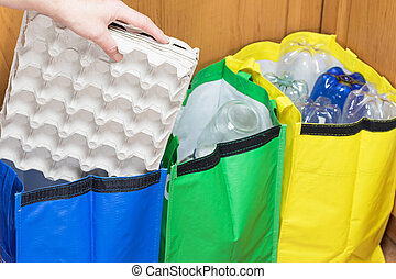 Sorting paper waste - Female hand is sorting paper packaging...