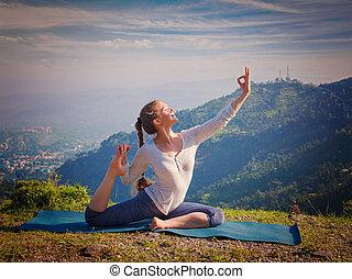 Yoga outdoors - young sporty fit woman doing stretching yoga asana Eka pada rajakapotasana - one-legged king pigeon pose in Himalayas mountains, India. Vintage retro effect filtered hipster style image.