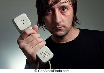 Sos phone line - MAn in black shirt holding a telephone, SOS...