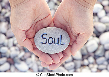 Woman holding stone with the word Soul in her palms