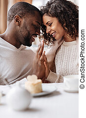 Soulful smiling African American couple touching hands in the cafe