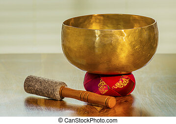 Sound bowl on a table with red bolster