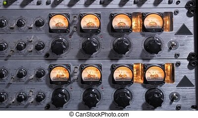 Closeup of adjustable handles and displays on compressor panel in professional record studio. Audio compressor reducing or compressing audio signal's dynamic range during sound recording in studio