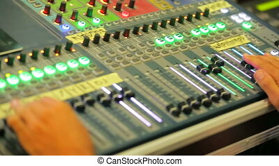 Close-up shot of hands of a technician sound engineer working with music mixing panel.
