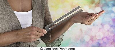 Sound Healer Using a Tuning Fork - Sound healer holding...