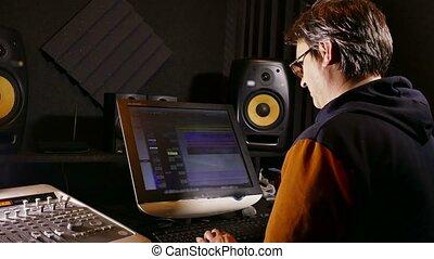 sound man designer in his recording studio - tracking shot -...