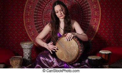 Sound of the drum - Young adult woman playing drum during...