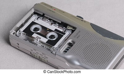 Sound recording on a hand-held portable vintage microcassette recorder. Hand puts the voice tape recorder and Rec interviews on a Mini Cassette. Rec of voice on a handheld player with 90s. 4K