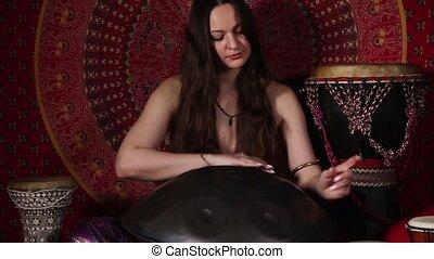 Sounds of hand pan - Tilt down video shot of a woman playing...