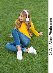 sounds of nature. relax on green grass. spring leisure time. happy childhood. kid in headset. happy little girl listen favorite song. kid beauty and fashion. teen girl listen music. education concept