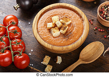 soup gazpacho on a wooden background in a wooden plate.