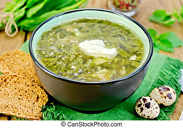 Soup green of sorrel and nettles with eggs on the board