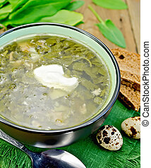Soup green of sorrel and spinach on board with eggs