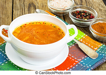 Soup in white bowl on wooden background.