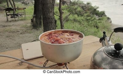 Soup is cooked outdoor on an gas cooker.