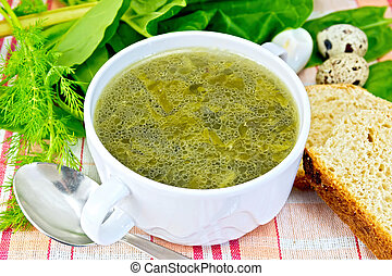 Soup of greenery with bread on cloth
