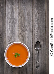 Soup on wood table - A bowl of tomato soup with a tarnished...