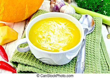 Soup-puree pumpkin with cream in white bowl on green napkin