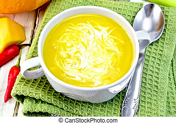 Soup-puree pumpkin with cream in white bowl on napkin