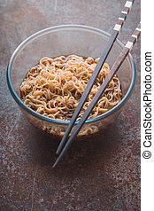 Soup Ramen noodles in glass bowl and on the gray table