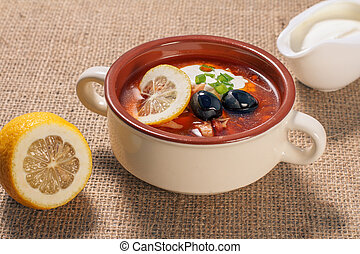 Soup saltwort with meat, potatoes, tomatoes, lemon and black olives in a bowl