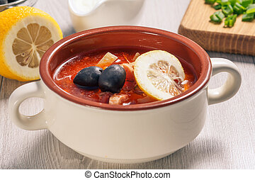 Soup saltwort with meat, potatoes, tomatoes, lemon and black olives