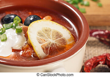 Soup saltwort with meat, potatoes, tomatoes, lemon, black olives and sour cream in ceramic soup bowl