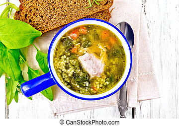Soup with couscous and spinach in blue bowl on board top