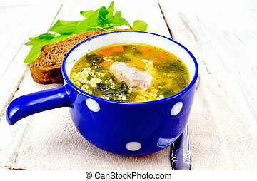 Soup with couscous and spinach in blue bowl on napkin