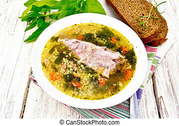 Soup with couscous and spinach in plate on light board