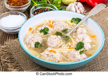 Soup with meatballs for dinner on wooden background