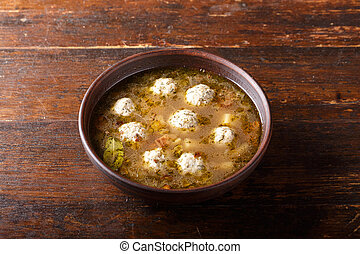 Soup with meatballs on a wooden background