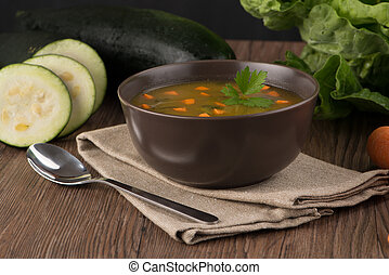 Soup with vegetables on wooden table.