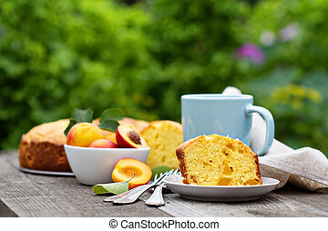Sour cream cake with nectarines served outside with tea