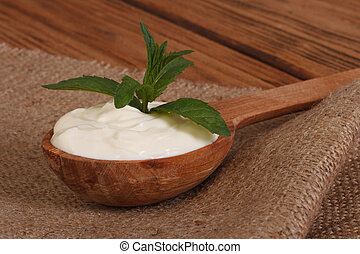 sour cream in a wooden spoon