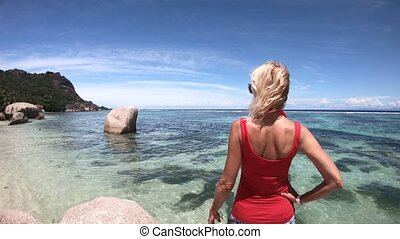 Source d'Argent La Digue - Tourist woman in red dress...