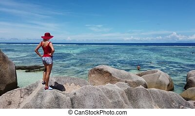 Source d'Argent La Digue - Tourist woman with in red dress...