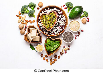 Sources of vegetable protein laid out in the shape of a heart on a white background