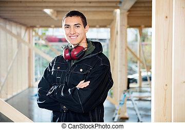 sourire, charpentier, debout, bras croisés, à, site