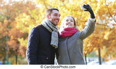 sourire, couple, à, smartphone, dans, automne, parc