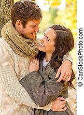 sourire, couple étreindre, dans, automne, parc