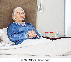 sourire, femme aînée, délassant, lit, à, clinique