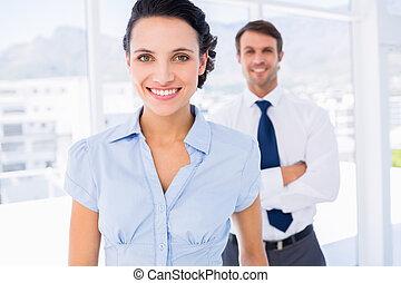 sourire, femme affaires, à, mâle, collègue, dans, fond