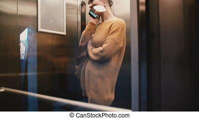 sourire., femme, mur verre, décontracté, jeune, ascenseur, haut, conversation, équitation, européen, téléphone, transparent, vue