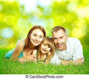 sourire heureux, jeune famille, amusant, dehors