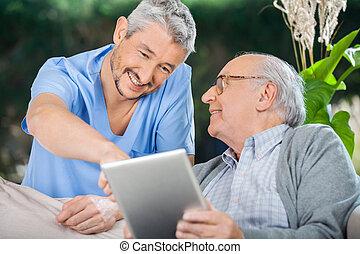 sourire, infirmière, aider, homme aîné, utilisation, dans, pc tablette