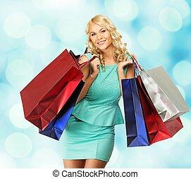 sourire, jeune, blonds, femme, à, sacs provisions, sur, arrière plan flou