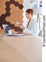 sourire, jeune femme, dans, a, moderne, espace bureau, à, téléphone