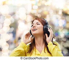sourire, jeune fille, dans, écouteurs, chez soi
