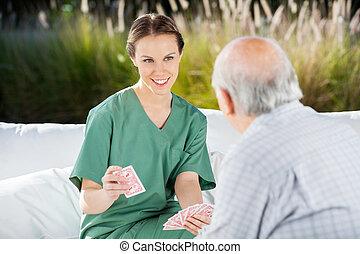 sourire, jouer, femme, cartes, infirmière, homme aîné